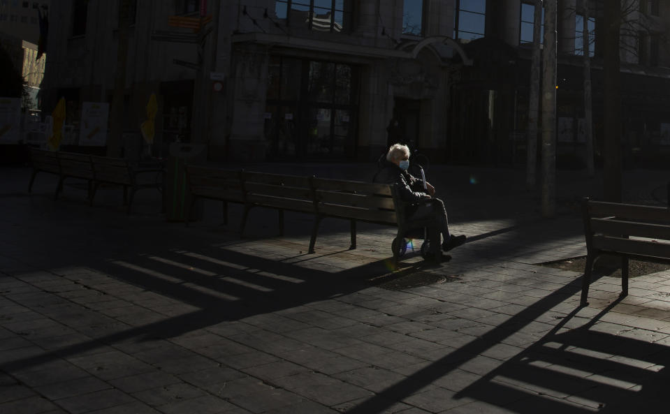 FILE - In this Tuesday, Nov. 3, 2020 file photo, a man sits alone on a park bench in the historical center of Antwerp, Belgium. The government on Monday, Feb. 22, 2021 presented scientific projections of the spread of the COVID-19 pandemic in Belgium, indicating it would be very risky to extensively loosen the current restrictions over the coming weeks. (AP Photo/Virginia Mayo, File)