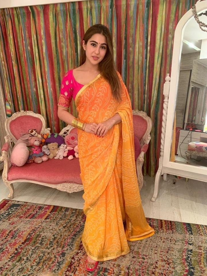 Bandhanis are known for their lively hues, two of which were picked by Sara Ali Khan this Diwali. Keeping her festive styling minimalist yet class apart from everyone else, the Pataudi girl picked a mango chiffon saree speckled with bandhej patterns. She paired the elegant 6 yards with an embroidered pink blouse and created the perfect contrast there is.