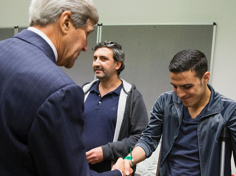US Secretary of State John Kerry (L) shakes hands with a man injured in a bomb attack in Syria during a meeting with a group of refugees fleeing Syria at Villa Borsig in Berlin on September 20, 2015 (AFP Photo/Evan Vucci)