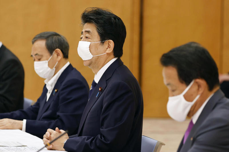 Japan's Prime Minister Shinzo Abe, center, speaks during a meeting of government and ruling party officials at his office in Tokyo Wednesday, May 27, 2020. Japan's Cabinet has approved a proposed 32 trillion-yen ($296 billion) supplementary budget to help fund measures to cushion the blow to the economy from the coronavirus pandemic. (Kyodo News via AP)