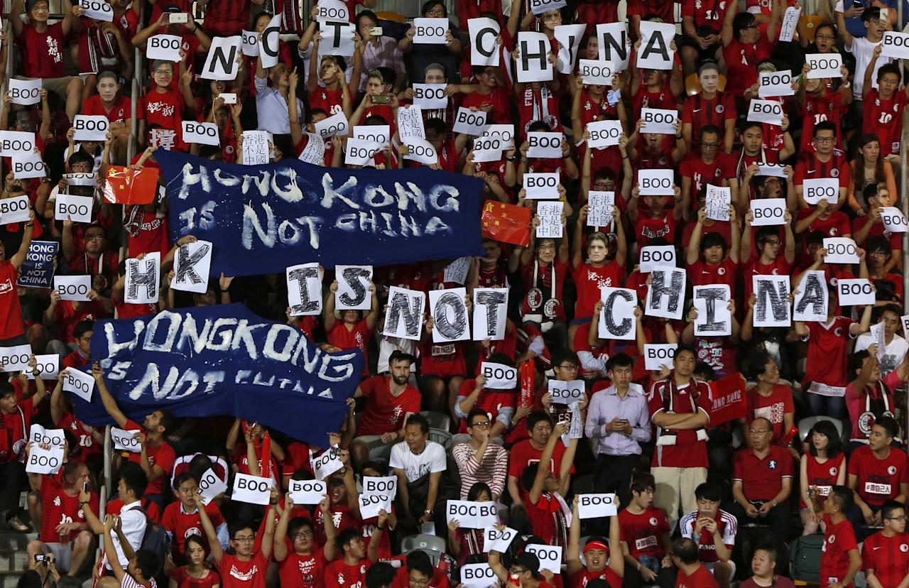 """Hong Kong fans hold banners and character signs which read """"Hong Kong is not China"""", during the 2018 World Cup qualifying match between Hong Kong and China, in Hong Kong, November 17, 2015. Less than a year after the Occupy protests, tensions were high going into match between Hong Kong and China. Fans booed the playing of the Chinese national anthem during the match, which ended in a 0-0 draw. REUTERS/Bobby Yip/File photo          SEARCH """"HONGKONG TIMELINE"""" FOR THIS STORY. SEARCH """"WIDER IMAGE"""" FOR ALL STORIES."""