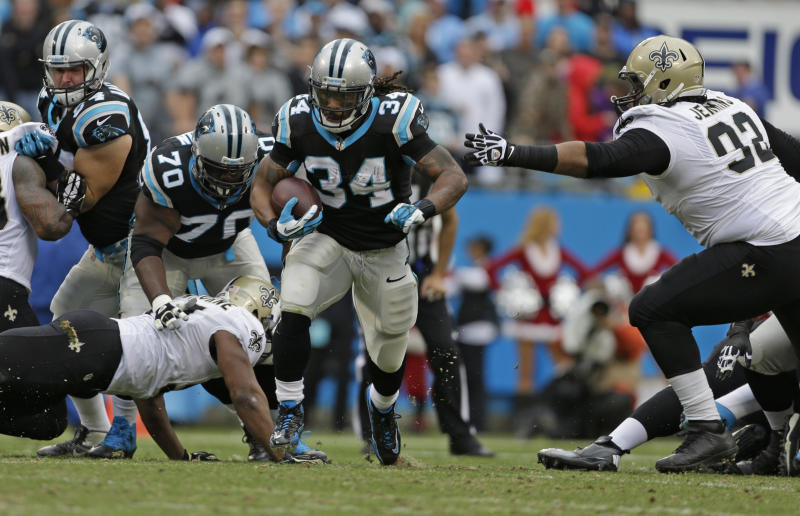 Carolina Panthers' DeAngelo Williams (34) breaks the tackle of New Orleans Saints' John Jenkins (92) for a touchdown run in the first half of an NFL football game in Charlotte, N.C., Sunday, Dec. 22, 2013. (AP Photo/Bob Leverone)