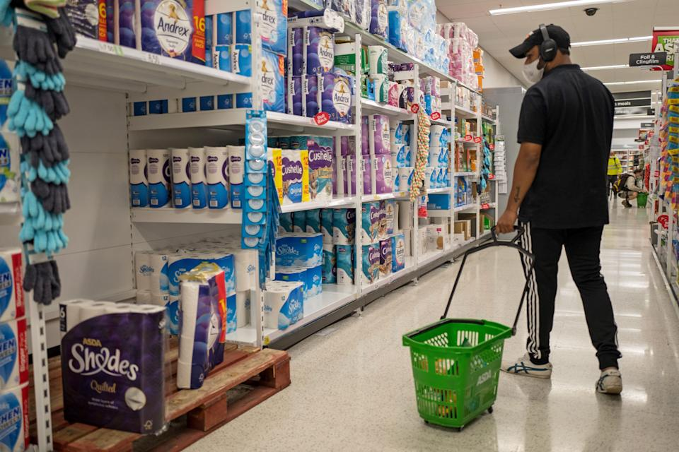 A man walks past the toilet paper in an Asda supermarket in Walthamstow, east London in Walthamstow, east London on September 23, 2020. - Britain on Tuesday tightened restrictions to stem a surge of coronavirus cases, ordering pubs to close early and advising people to go back to working from home to prevent a second national lockdown. (Photo by Tolga AKMEN / AFP) (Photo by TOLGA AKMEN/AFP via Getty Images)