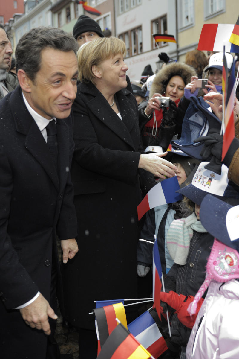France's President Nicolas Sarkozy and German Chancellor Angela Merkel are cheered by children on the Munster Square in Freiburg, southern Germany, Friday, Dec. 10, 2010. President Nicolas Sarkozy and Chancellor Angela Merkel met on Friday to prepare joint Franco-German positions for next week's EU summit .  (AP Photo/Philippe Wojazer, pool)