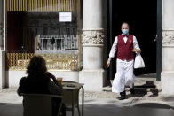 FILE - In this Monday, May 18, 2020 file photo, a waiter, wearing a protective face mask, brings an order to a customer sitting outdoors at the Versailles restaurant and pastry shop in Lisbon, Portugal. The coronavirus pandemic is gathering strength again in Europe and, with winter coming, its restaurant industry is struggling. The spring lockdowns were already devastating for many, and now a new set restrictions is dealing a second blow. Some governments have ordered restaurants closed; others have imposed restrictions curtailing how they operate. (AP Photo/Armando Franca, File)