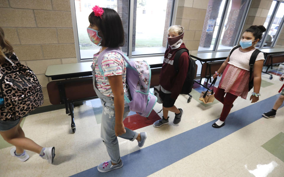Wearing masks to prevent the spread of COVID19, elementary school students walk to class to begin their school day in Godley, Texas, Wednesday, Aug. 5, 2020. Three rural school districts in Johnson County were among the first in Texas to head back to school for in person classes for students. (AP Photo/LM Otero)