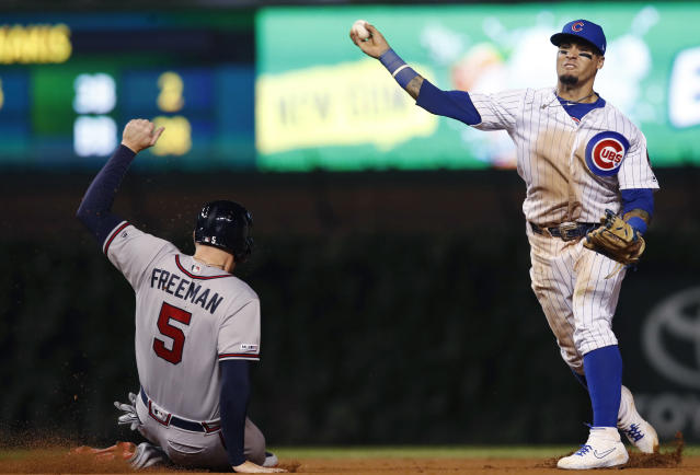 Atlanta Braves' Freddie Freeman, left, is out sliding into second base as Chicago Cubs' Javier Baez, right, throws to first base during the eighth inning of a baseball game Monday, June 24, 2019, in Chicago. (AP Photo/Jim Young)