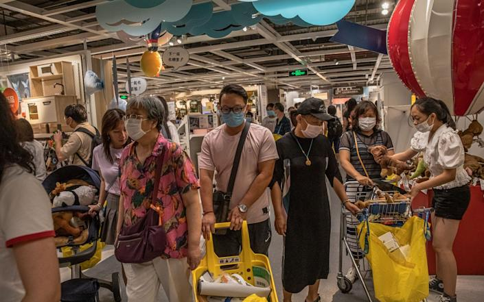 Shoppers wearing face coverings browse an IKEA store in Beijing, where more than 300 people have been infected with the virus since June - Shutterstock