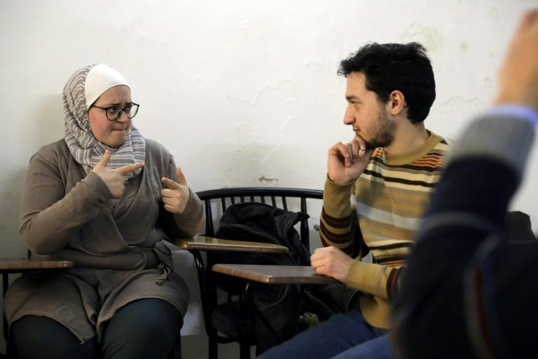 Syrian bio-medical engineer and sign language teacher Wisal al-Ahdab (L) communicates using sign language with 21-year-old deaf student Riyad Hommos during a class at the EEMAA association, an NGO centre in Damascus' Midan district