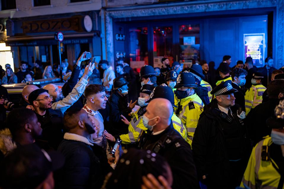 <p>Police officers attempt to keep the crowd away from a police van after a man was arrester on Old Compton Street in Soho</p> (Getty Images)