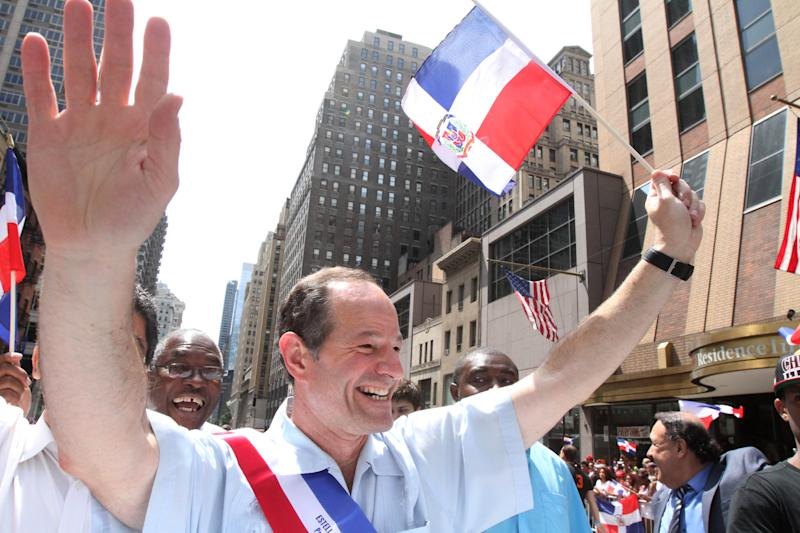 Eliot Spitzer, running for NYC Comptroller, foreground, waves as he makes his way up New York's Avenue of the Americas during the Dominican Day Parade Sunday Aug. 11, 2013. (AP Photo/Tina Fineberg)