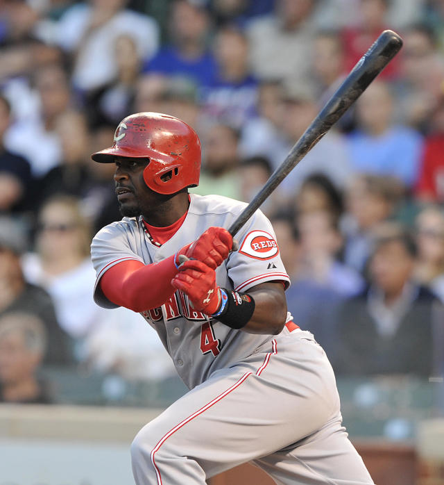 Cincinnati Reds' Brandon Phillips singles in a run against the Chicago Cubs during the first inning of a baseball game Tuesday, Aug. 13, 2013, in Chicago. (AP Photo/Jim Prisching)
