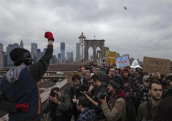 An Occupy Wall Street protester raises his fist towards dozens of fellow activists marching across the Brooklyn Bridge in New York April 1, 2012.