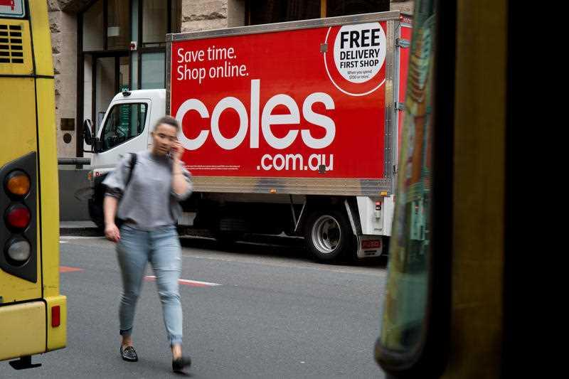 A woman walks past a Coles delivery truck.