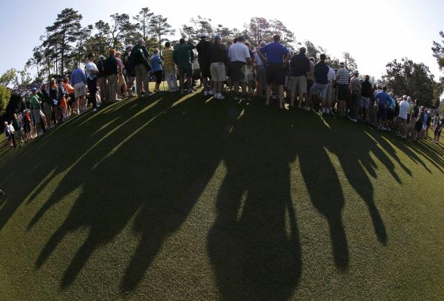 Patrons gather around the first green during the second round of the Masters golf tournament at the Augusta National Golf Club in Augusta, Georgia April 11, 2014. REUTERS/Mike Segar (UNITED STATES - Tags: SPORT GOLF)
