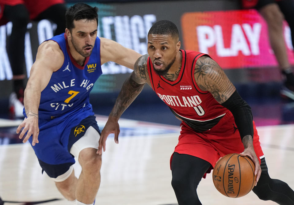 Portland Trail Blazers guard Damian Lillard (0) drives past Denver Nuggets guard Facundo Campazzo (7) in the second half of Game 1 of a first-round NBA basketball playoff series Saturday, May 22, 2021, in Denver. (AP Photo/Jack Dempsey)