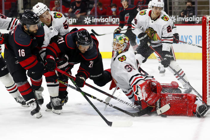 Carolina Hurricanes' Nino Niederreiter (21) and Vincent Trocheck (16) battle with Chicago Blackhawks' Ian Mitchell (51) and goaltender Collin Delia (60) with Blackhawks' Pius Suter (24) looking on during the second period of an NHL hockey game in Raleigh, N.C., Monday, May 3, 2021. (AP Photo/Karl B DeBlaker)