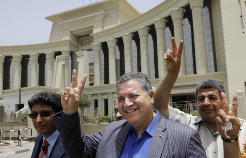 Hamdy El-Fakharany, an opposition leader and former member of the now-dissolved Parliament, center, and other activists flash victory signs in front of the Supreme Constitutional Court in Cairo, Egypt, Sunday, June 2, 2013. An Egyptian court ruled on Sunday that the nation's Islamist-dominated legislature and constitutional panel were illegally elected and that the legislature's upper house, the only one currently sitting, must be dissolved when parliament's lower chamber is elected later this year or early in 2014. (AP Photo/ Amr Nabil)