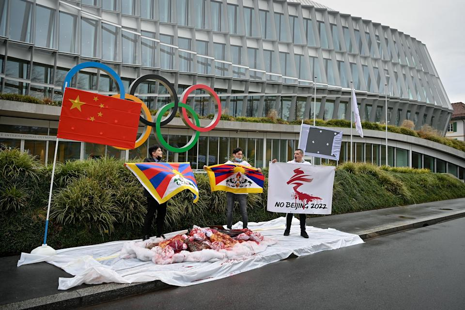 Activists of the International Tibet Network holds Tibet's flags in front of the IOC headquarters during a protest against Beijing 2022 Winter Olympics on February 3, 2021 in Lausanne. - A coalition of campaign groups issued an open letter calling on world leaders to boycott the Beijing 2022 Winter Olympics over China's rights record. The Games are scheduled to begin on February 4 next year, just six months after the delayed summer Tokyo Olympics, but preparations have been overshadowed by the coronavirus pandemic. (Photo by Fabrice COFFRINI / AFP) (Photo by FABRICE COFFRINI/AFP via Getty Images)