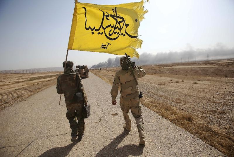 Iraqi Shiite fighters from the Popular Mobilisation units, show their flag in Baiji north of Tikrit (AFP Photo/Mohammed Sawaf)