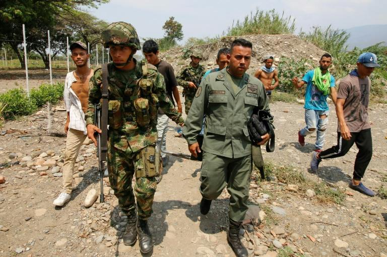 A Colombian soldier escorts a Venezuelan defector who crossed the border to Cucuta, Colombia