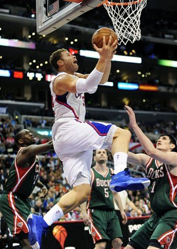 Los Angeles Clippers forward Blake Griffin, center, battles by Milwaukee Bucks forward Ekpe Udoh, left, guard J.J. Redick (5) and forward Ersan Ilyasova (7), of Turkey, for a reverse dunk in the first half of an NBA basketball game, Wednesday, March 6, 2013, in Los Angeles.(AP Photo/Gus Ruelas)