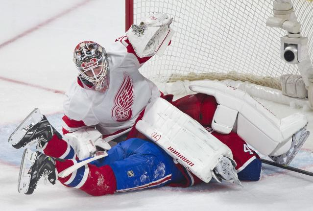 Detroit Red Wings goaltender Jonas Gustavsson falls on Montreal Canadiens' Michael Bournival during the second period of an NHL hockey game in Montreal, Saturday, April 5, 2014. (AP Photo/The Canadian Press, Graham Hughes)
