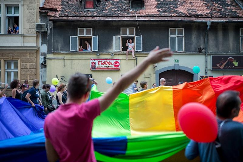 Residents watch the Gay Pride parade passing through their street in Ljubljana, Slovenia, on June 14, 2014