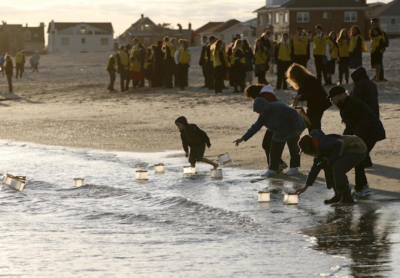 """Rockways residents float lanterns containing handwritten personal messages in the water at the conclusion of """"Rockaways Rising: Hands Scross the Sand,"""" commemorating the one year anniversary of Superstorm Sandy, Sunday, Oct. 27, 2013, in New York. The actual one year anniversary of Superstorm Sandy is Tuesday, Oct. 29. (AP Photo/Kathy Willens)"""
