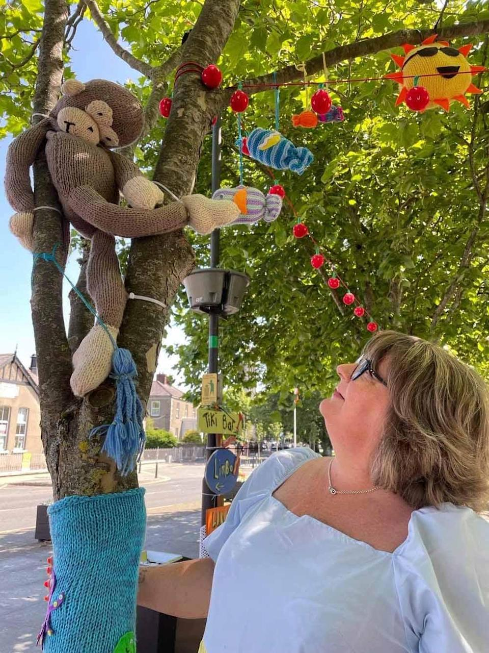 Monica with a knitted monkey in the yarn bombed town centre (Collect/PA Real Life).