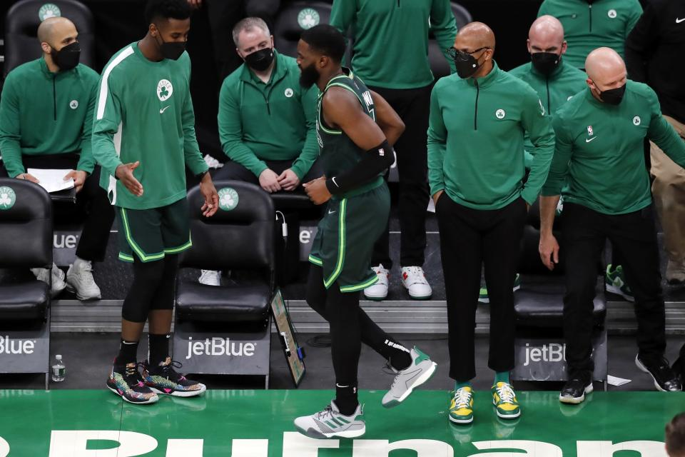 Boston Celtics' Jaylen Brown, center, limps off the court after colliding with teammate Jayson Tatum during the second half of an NBA basketball game against the Portland Trail Blazers, Sunday, May 2, 2021, in Boston. (AP Photo/Michael Dwyer)