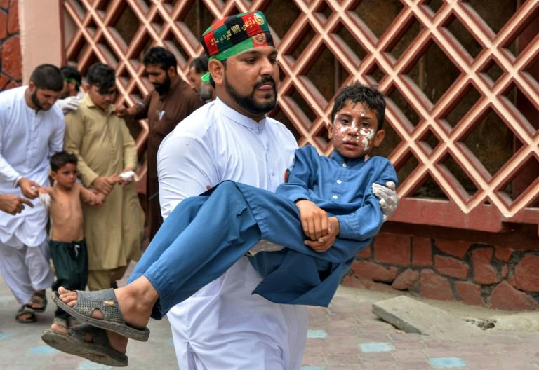 A volunteer carries an injured boy to a hospital in Jalalabad
