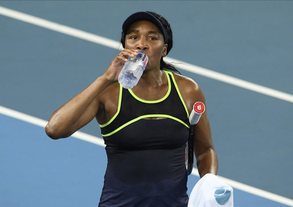 """United States' Venus Williams takes a drink during their first round singles match against compatriot Cori """"Coco"""" Gauff at the Australian Open tennis championship in Melbourne, Australia, Monday, Jan. 20, 2020. (AP Photo/Andy Brownbill)"""