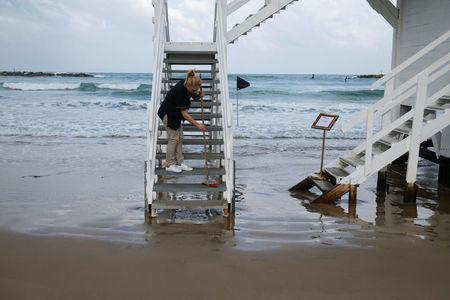 A woman cleans the stairs of a lifeguard tower before the winners of an international online competition arrive to spend a night at the tower which was renovated into a luxury hotel suite, at Frishman Beach in Tel Aviv, Israel March 14, 2017. REUTERS/Baz Ratner