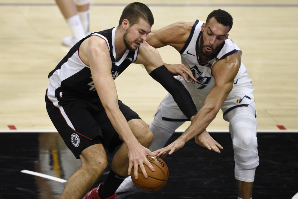 Los Angeles Clippers center Ivica Zubac, left, attempts to drive the ball to the basket while pressured by Utah Jazz center Rudy Gobert during the first half of an NBA basketball game in Los Angeles, Friday, Feb. 19, 2021. (AP Photo/Kelvin Kuo)
