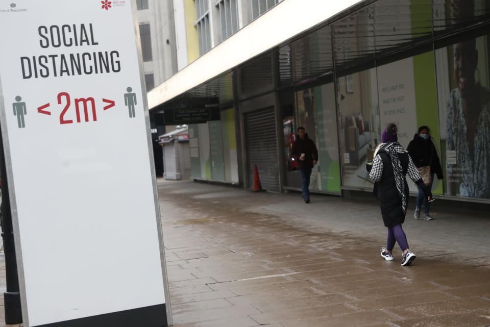 Pedestrians walk past a sign advising them to keep 2 meters apart on Oxford Street in London, Tuesday, Jan. 26, 2021. The U.K. will soon become the fifth country in the world to record 100,000 COVID-19 deaths, after the United States, Brazil, India and Mexico — all of which have much larger populations than Britain's 67 million people. As of Monday, the U.K.'s official coronavirus death toll was 98,531. (AP Photo/Alastair Grant)