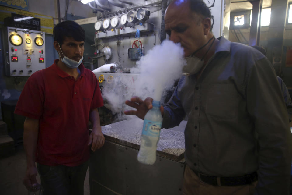 A man tests oxygen at a privately owned oxygen factory, in Kabul, Afghanistan, Thursday June 18, 2020. For seven years, Najibullah Seddiqi's oxygen factory sat idle in the Afghan capital Kabul. He shut it down, he says, because corruption and power cuts made it impossible to work. But when the novel coronavirus began racing through his country, he opened the factory's dusty gates and went back to work. Now he refills hundreds of oxygen cylinders a day for free for COVID-19 patients — and at reduced rates for hospitals. (AP Photo/Rahmat Gul)