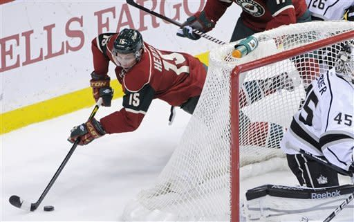 Minnesota Wild's Dany Heatley, left, falls as he tries to maintain control of the puck behind Los Angeles Kings goalie Jonathan Bernier in the first period of an NHL hockey game Tuesday, Feb. 28, 2012 in St. Paul, Minn. (AP Photo/Jim Mone)