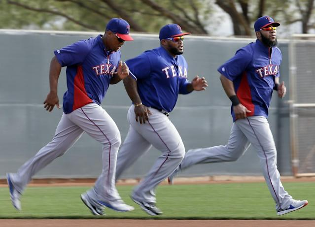Texas Rangers' Adrian Beltre, left, Prince Fielder and Elvis Andrus, right, jog across the field as they warm up before a workout during spring training baseball practice, Wednesday, Feb. 19, 2014, in Surprise, Ariz. (AP Photo/Tony Gutierrez)