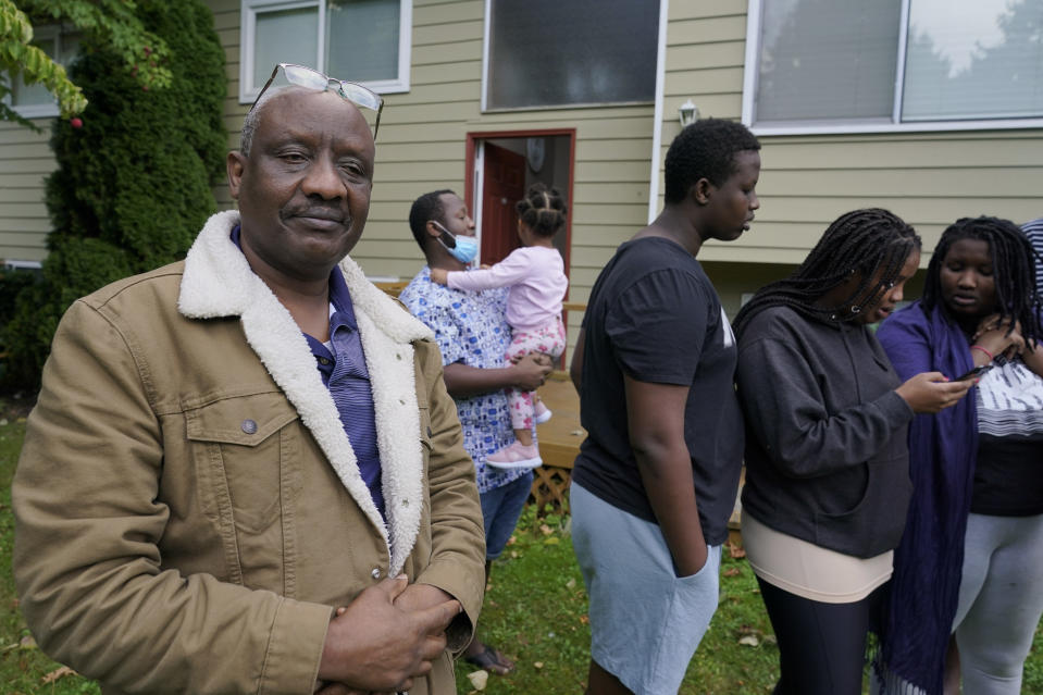 Sophonie Bizimana, left, a permanent U.S. resident who is a refugee from Congo, stands in front of his home in Kirkland, Wash., Wednesday, Oct. 14, 2020, as some of his children look at photos on their phones. Bizimana's wife, Ziporah Nyirahimbya, is in Uganda and has been unable so far to join him in the U.S. For decades, America admitted more refugees annually than all other countries combined, but that reputation has eroded during Donald Trump's presidency as he cut the number of refugees allowed in by more than 80 percent. (AP Photo/Ted S. Warren)