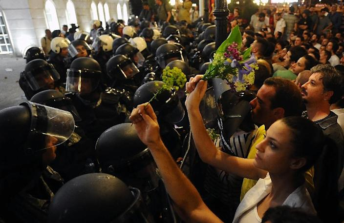 Macedonian demonstrators hold flowers in front of riot policemen during a protest outside the government building in Skopje on May 5, 2015 (AFP Photo/Robert Atanasovski)