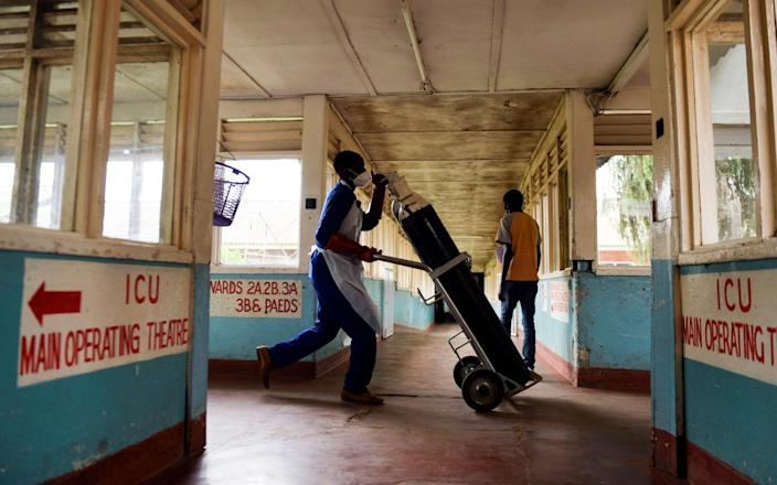 A health worker takes oxygen cylinders to COVID-19 wards at Queen Elizabeth Central Hospital in Blantyre, Malawi - AP Photo/Thoko Chikondi