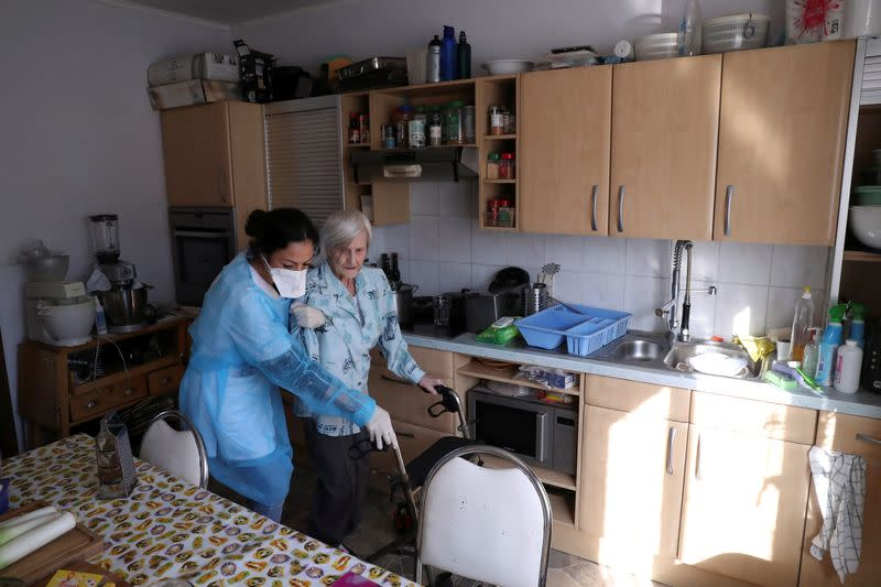Belgian home nurse Hajar Atila takes care of her patient Anna Edith Slepicka at her home during the coronavirus lockdown in Belgium