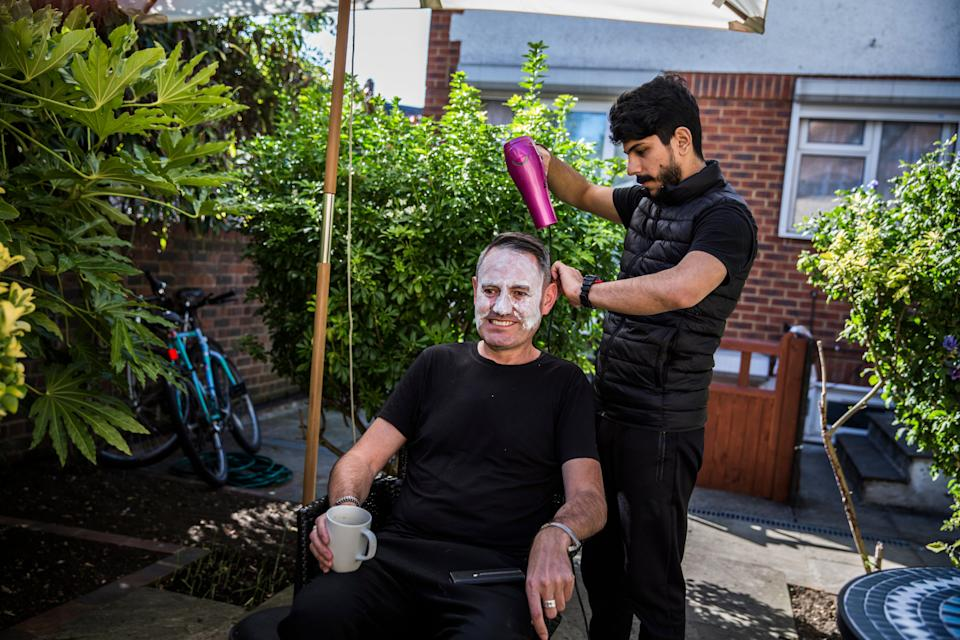 <p>Syrian refugee Lutfi Al-Shaabin, who worked as a barber in Jordan where his family lived as refugees, cuts Tim Finch's hair at the Al-Shaabin home in south London</p>Andrew McConnel