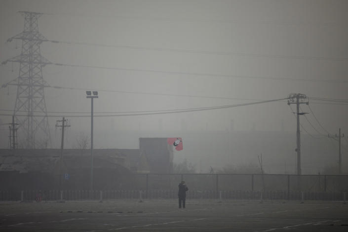 FILE - In this Jan. 12, 2013 photo, a man flies a kite near electricity pylons on a hazy day in Beijing. While the numbers are hard to quantify, executive recruitment consultants say they are noticing that it is becoming harder to attract top talent to China - both expats and Chinese nationals educated abroad. If the polluted skies continue, companies may have to fork out more money for their workers, settle for less qualified candidates or hire local workers instead of expats. (AP Photo/Alexander F. Yuan, File)
