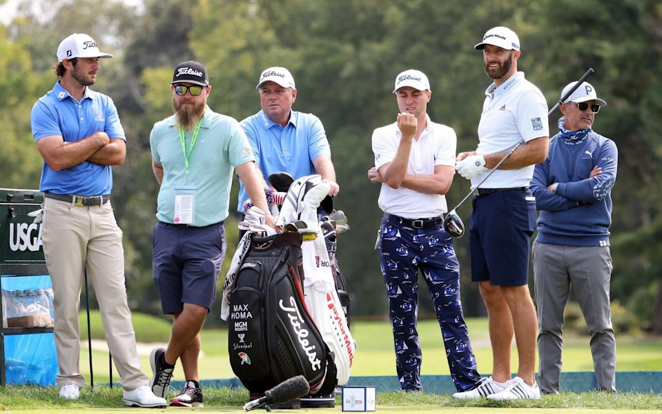 Max Homa of the United States, Justin Thomas of the United States and Dustin Johnson of the United States look on from the second tee during a practice round - GETTY