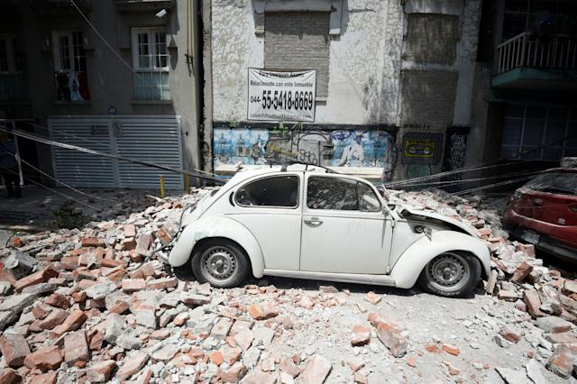 A car is crushed by debris from a damaged building.