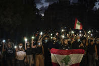 Demonstrators march holding candles and flashlights honoring the victims of the deadly explosion at Beirut port which devastated large parts of the capital, in Beirut, Lebanon, Sunday, Aug. 9, 2020. (AP Photo/Felipe Dana)