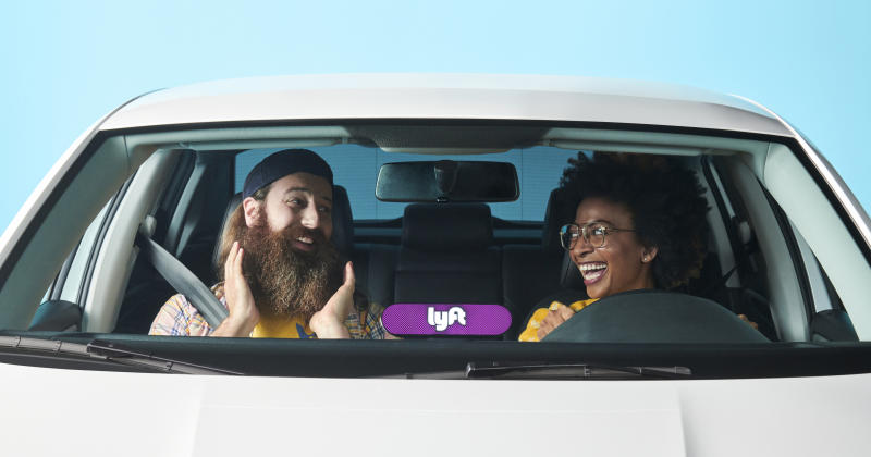 A Lyft driver and rider in a car having fun.