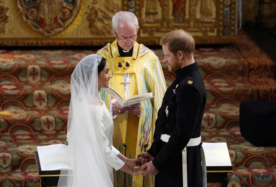 TOPSHOT - Britain's Prince Harry, Duke of Sussex (R) and US actress Meghan Markle (L) stand facing each other hand-in-hand before Archbishop of Canterbury Justin Welby (C) during their wedding ceremony in St George's Chapel, Windsor Castle, in Windsor, on May 19, 2018. (Photo by Owen Humphreys / POOL / AFP)        (Photo credit should read OWEN HUMPHREYS/AFP via Getty Images)